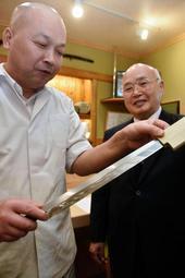 CNT入り刺し身包丁の出来栄えを確認する松原賢政社長(右)と米沢信吾さん=姫路市土山5