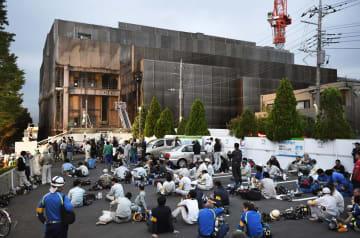 火災のあった建設現場(奥)と避難した作業員ら=7月、東京都多摩市