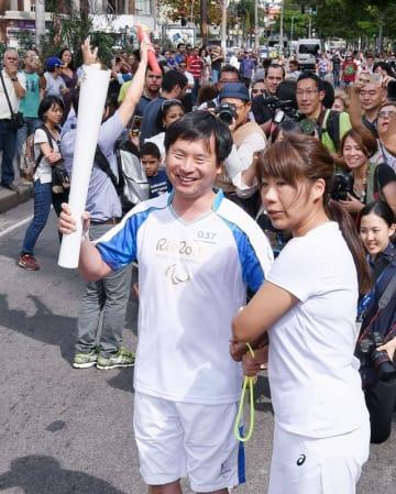 2016年9月、リオデジャネイロ・パラリンピックの聖火リレーで、トーチを持つ日本パラリンピアンズ協会の河合純一会長(共同)