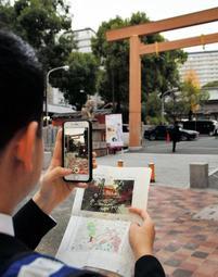 阪神・淡路大震災当時の被災写真を現地で見ながら、情報を送る職員=神戸市中央区
