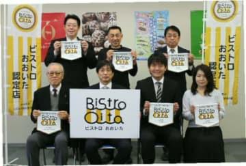 認定フラッグを持つビストロおおいた認定店の関係者と中島英司県農林水産部長(前列左から2人目)=21日、県庁