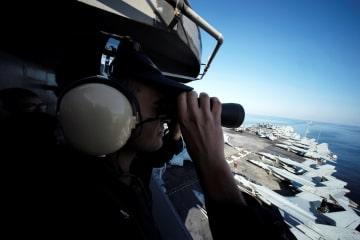 21日、ホルムズ海峡からペルシャ湾に向かう米海軍の原子力空母ジョン・ステニスの艦橋から監視する米軍兵士(ロイター=共同)
