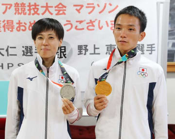 アジア大会のマラソンでメダルを手にした男子の井上(MHPS、右)と女子の野上(十八銀行)。地元に帰ってきて多くの祝福を受けた=長崎市役所