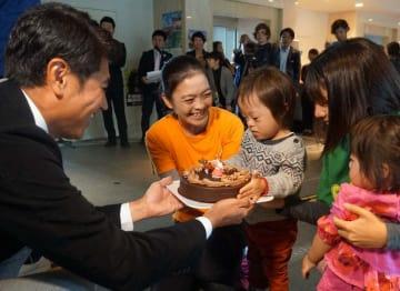 竹内一郎社長(左)からクリスマスケーキを受け取る子=21日、那覇市首里石嶺町・県総合福祉センター