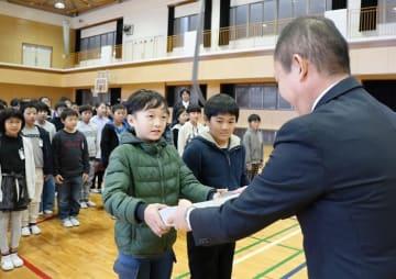 渡邊部長(右)からカレンダーを受け取る児童=長崎市立大浦小