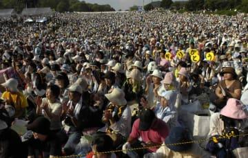 手に「ありがとう」のうちわを持ち、平和を願い歌い続けるさださんを励ます会場いっぱいのファン=長崎市稲佐山公園野外ステージ
