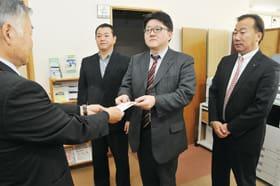 菅野理事長に、善意を手渡す大坂会長(右から2人目)ら室蘭東LCの関係者ら