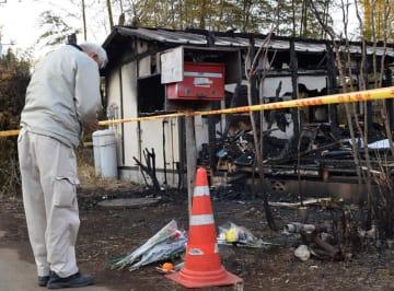全焼した海老原さん宅に手を合わせる男性=2月23日、印西市竜腹寺