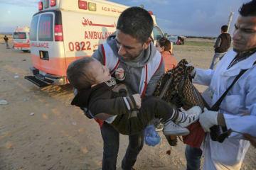 21日、パレスチナ自治区ガザで、イスラエル軍による攻撃の後、負傷して運ばれる子供(アナトリア通信・ゲッティ=共同)