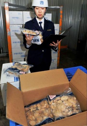 輸入された鶏の唐揚げを調べる横浜税関職員=川崎市川崎区の冷凍倉庫