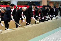 安全な工事や早期整備を願い、くわ入れに臨む関係者ら=22日午前、神戸市東灘区向洋町中2