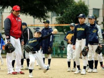畝コーチ(左端)から投球のこつを教わり、キャッチボールする小学生