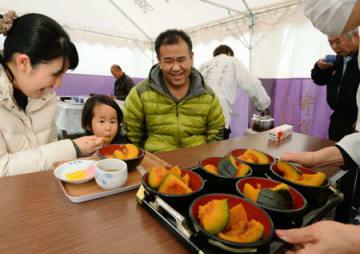 炊きたてのカボチャを食べる参拝者(22日午前10時30分、京都市北区・不思議不動院)