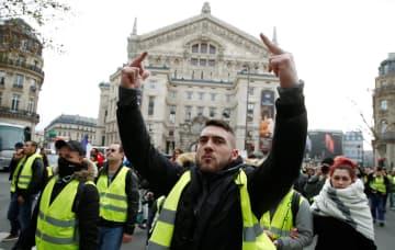 22日、黄色いベストを着てパリ中心部でのデモに参加する人々(ロイター=共同)
