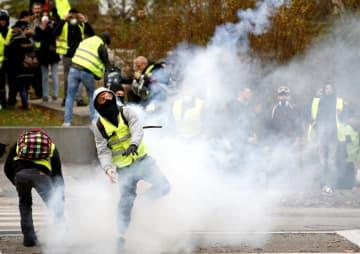 22日、フランス西部ナントで、警察と衝突する黄色いベスト運動のデモ参加者(ロイター=共同)