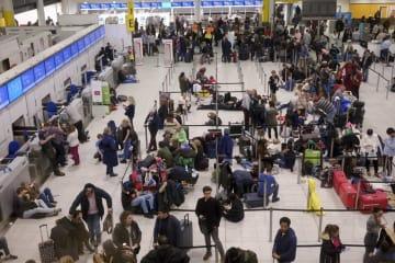 20日、ロンドン近郊のガトウィック空港で待つ人々(AP=共同)