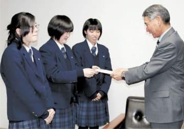 集めた義援金を佐藤市長に託す生徒代表の3人