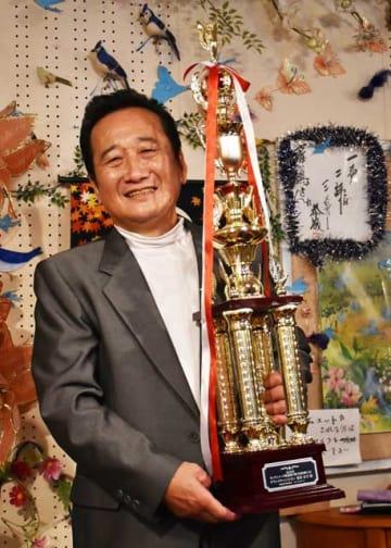カラオケの全国大会で悲願のグランドチャンピオンに輝いた粟栄安幸さん