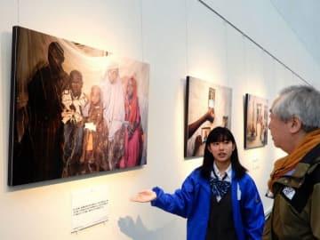 アフリカの人道危機を伝える写真を解説する大塚さん(左) =横浜市西区