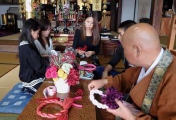 【参加者らにしめ飾りの作り方を指導する堤さん(中央)=亀山市菅内町の長賢寺で】