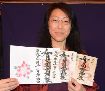 24日に抽選で配布する御朱印を持つ柏倉さん(右側2枚が和紙)