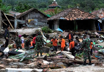 津波被災地で捜索活動をする救助隊=23日、インドネシア・ランプン州(ロイター=共同)