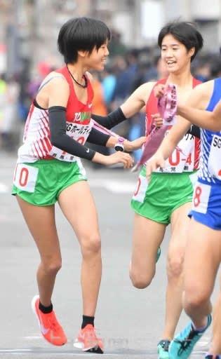 女子 常磐の4区飯嶋(右)からアンカー松崎にたすきが渡る=京都・第4中継所(西大路下立売)