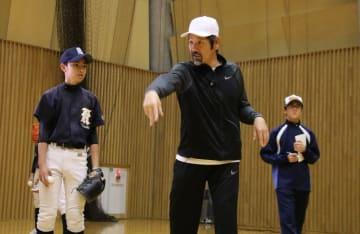 中学生に投球フォームを指導する下柳さん(中央)=五島市中央公園市民体育館