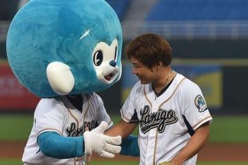 始球式を終え、ラミゴのマスコット「猿気小子」と握手する美崎信二さん=台湾桃園市の桃園国際球場