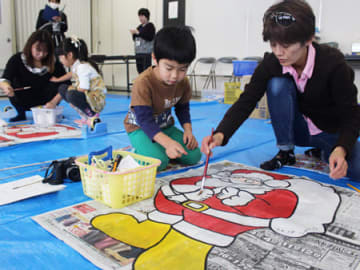 サンタクロースの凧に色を塗る親子ら(東近江市・東近江大凧会館)