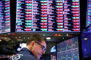 ニューヨーク証券取引所のトレーダーと電光掲示板=24日(ロイター=共同)