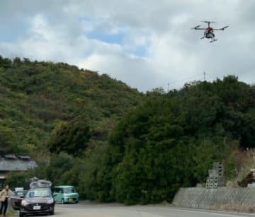 模擬血液検体を載せたドローン(右上)が約8キロのルートを自動飛行した実証実験=広島県大崎上島町(シーアイロボティクス提供)