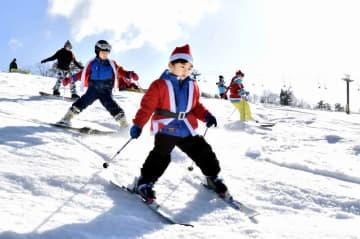 サンタ姿で滑りを楽しむ子どもたち=12月24日、福井県勝山市のスキージャム勝山