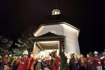 24日、生誕200年の聖歌「きよしこの夜」を、オーストリア・オーベルンドルフのゆかりの礼拝堂で歌う人たち(共同)