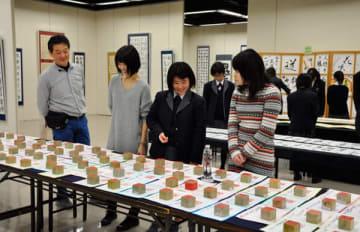 【展示作品を鑑賞する生徒ら=四日市市安島の市文化会館で】