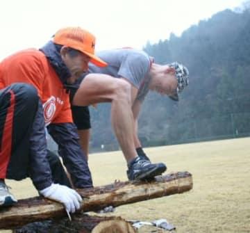 ゴール直前で丸太を切る出場者(右)=日田市二串の萩尾公園