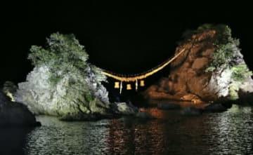 ライトアップされ、海に浮かび上がる豊後二見ケ浦の夫婦岩=24日午後6時10分、佐伯市上浦