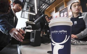 北京の瑞幸珈琲店。客(左)がスマホを読み取り機にかざしてコーヒーを受け取る=10月(共同)