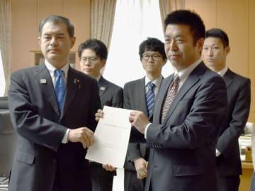 文科省の中堅・若手職員有志から報告書を受け取る柴山文科相(左)=25日午前、文科省