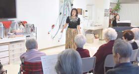 クリスマスソングや往年の名曲を歌い、入居者らを和ませる菅原さん(正面)