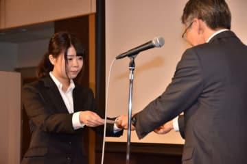 米倉明道社長から内定証書を受け取る佐藤優香さん(左)