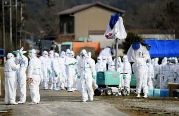 豚コレラが発生した養豚場に集まった防護服の作業員=25日午前11時41分、岐阜県関市