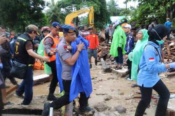 インドネシア・バンテン州で倒壊したホテルから救出された負傷した少年を運ぶ警察官(手前中央)=23日(地元警察提供・UPI=共同)