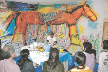 荒井さん(中央)の壁画制作を間近で見る参加者