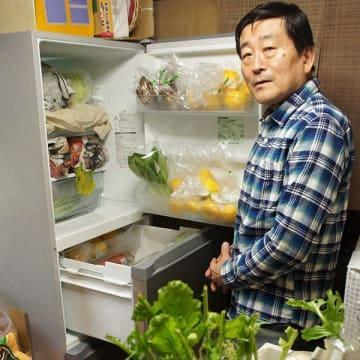 寄せられた食材でいっぱいになった冷蔵庫と、台所に置かれた野菜などに囲まれる中臺博さん=相模原市南区