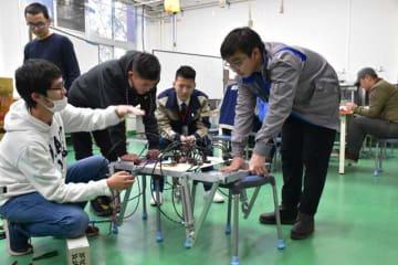 都城高専生(左)と相談しながら4足歩行ロボットを試作するモンゴルの高専生ら