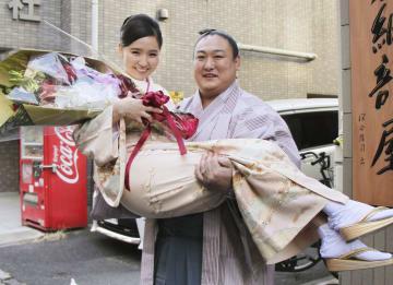 ソフダエルデネ夫人(左)を抱き上げる旭秀鵬=25日、東京都墨田区の友綱部屋