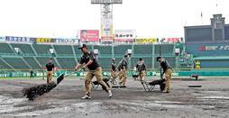 プロ野球クライマックスシリーズの試合前、雨でぬかるんだグラウンドを整備する阪神園芸のスタッフ=2017年10月17日、阪神甲子園球場