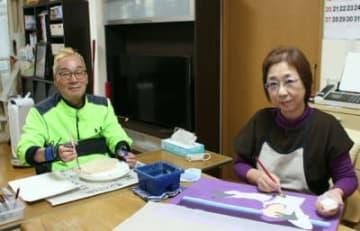 「体が動く限り描き続けたい」と制作に取り組む松崎吉信さん(左)と雅子さん夫婦=大分市