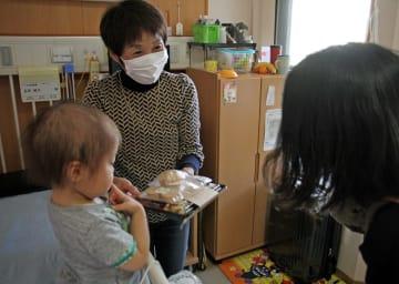 新井さん(右)から弁当を受け取った患者家族=長崎大学病院
